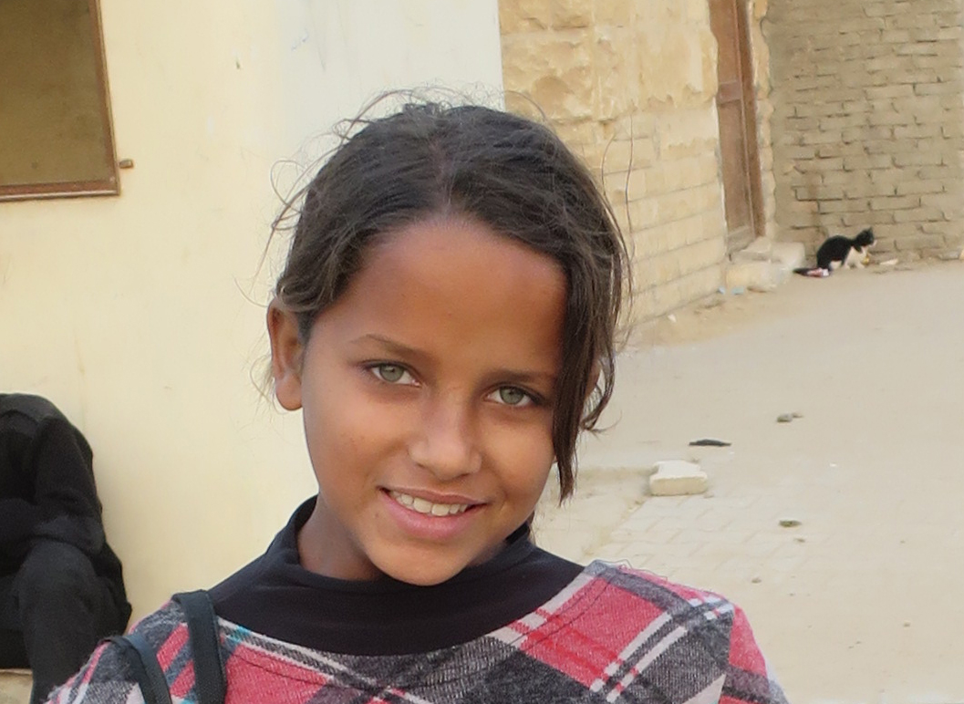 I estimate her age to be 13, her family lives on the edge of society, she is sent everyday to the pyramids to sell stuff, she speaks very good tourist English, she had these incredible green eyes